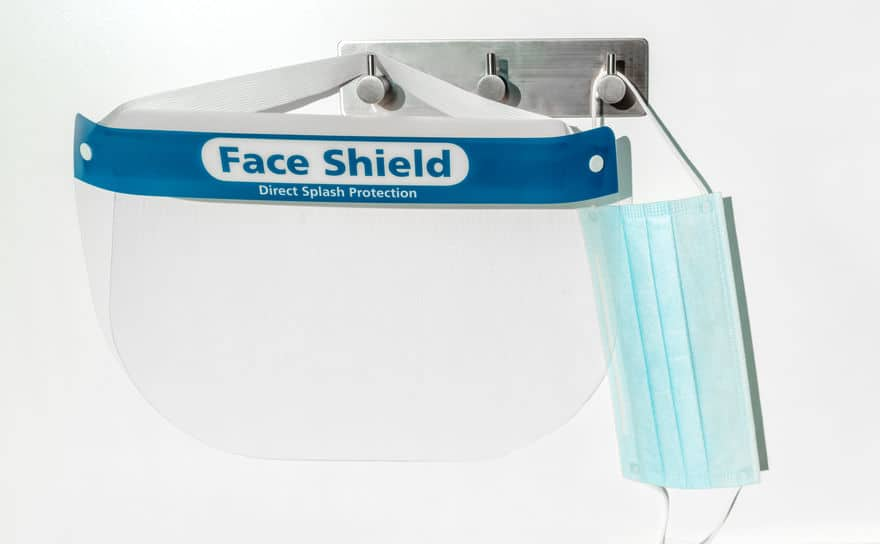 PPE supplies face shield direct splash protection and mask hanging on hooks. New clean corona virus protective equipment ready to use for coronavirus prevention