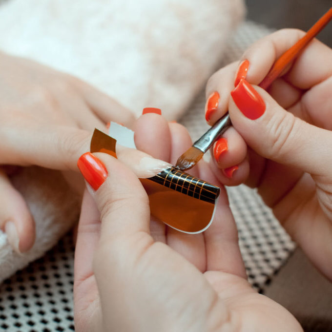 The master of the nail polish puts a fixative on the finger before making the nails gel in the beauty salon. Professional care for hands.