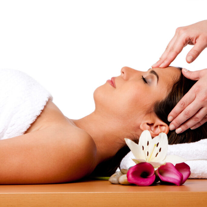Beautiful happy peaceful sleeping woman at a spa, laying on wooden massage table with head on pillow wearing a towel getting a facial massage, isolated.