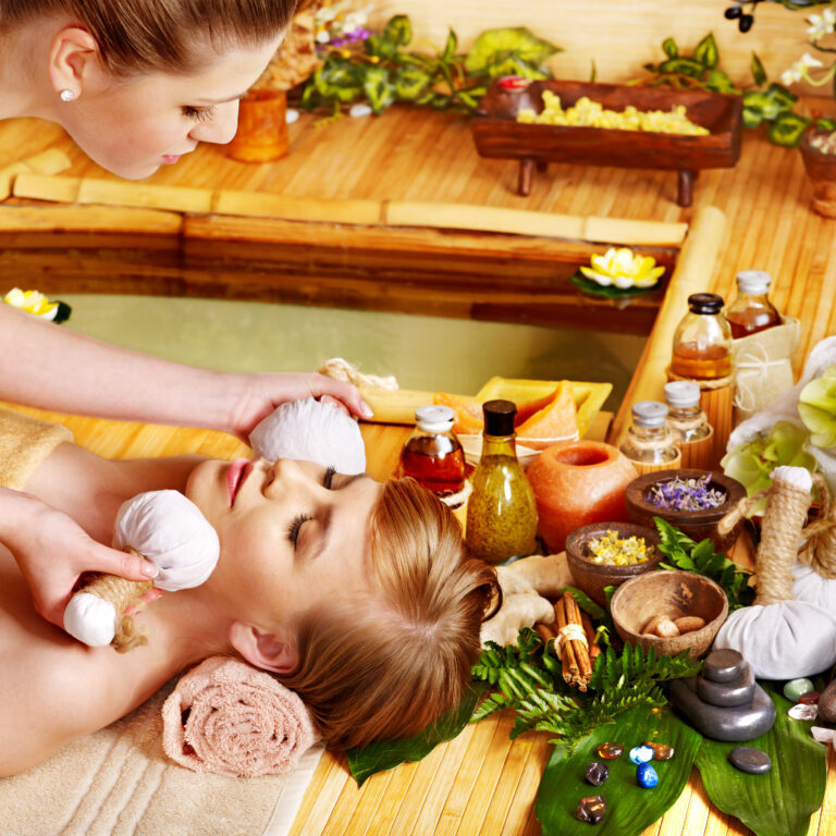 Young woman getting facial herbal massage ball.