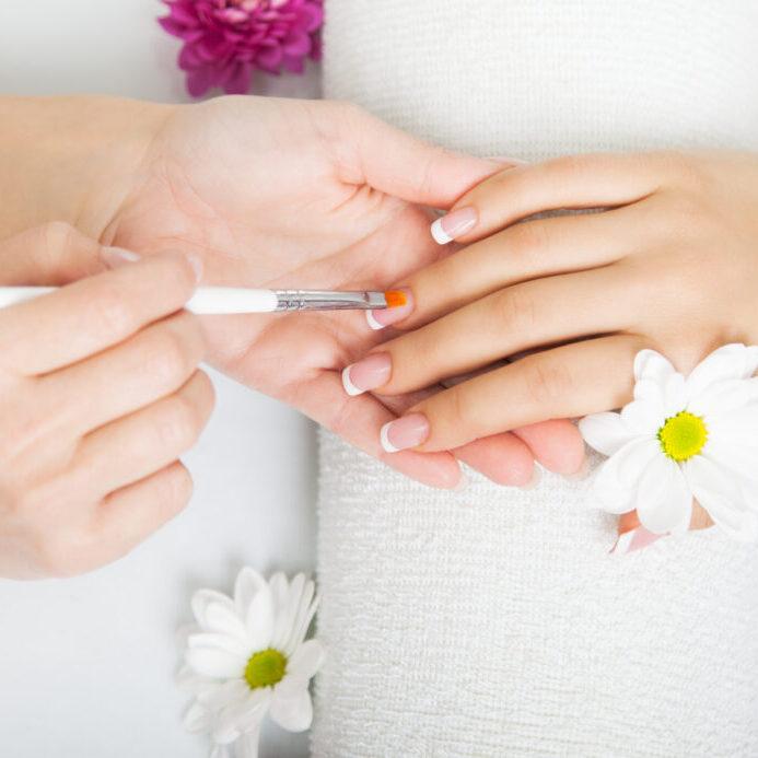 Beautician applying gel on fingernails