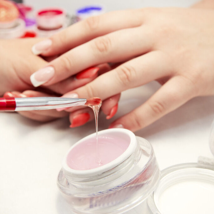Artificial nails in a beauty salon. Hands close-up. The process of nails.