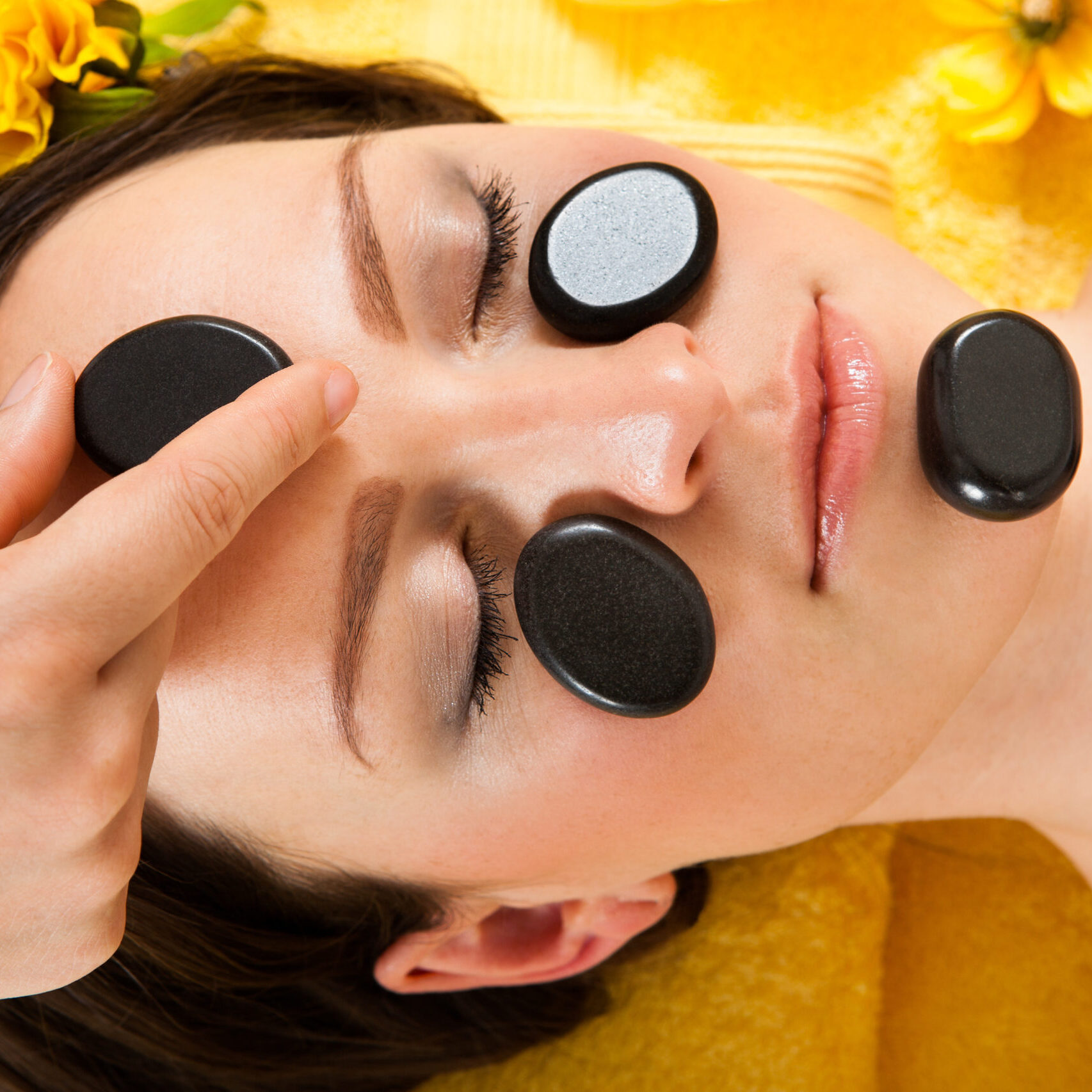Directly above of beautiful woman receiving hot stone therapy on face in spa